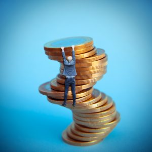 businessman hanging on euro coins column