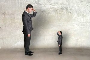 Big businessman and small businessman watch each other - unequal competition concept